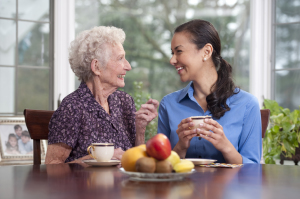Caregiver and elderly woman enjoying a hot beverage