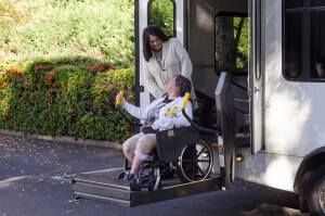 senior using wheelchair lift on van with caregiver